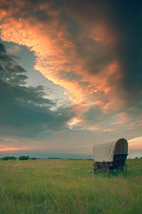Lone covered wagon heading towards the setting sun over Nebraska prairie at Rock Creek State Historic Park, Nebraska.