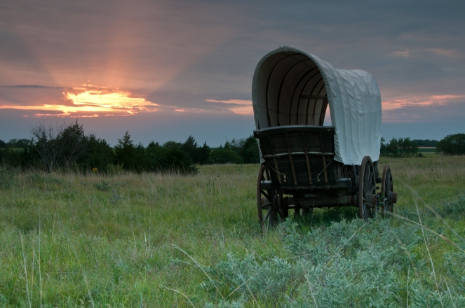 Lone covered wagon heading towards the setting sun over Nebraska prairie at Rock Creek State Historic Park, Nebraska.