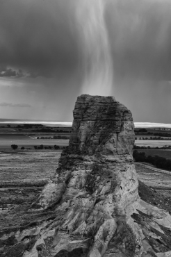 Narrow rain squall falling behind Jail Rock viewed from Courthouse Rock. Both Jail and Courthouse Rocks were important landmarks along the Oregon Trail, Nebraska.