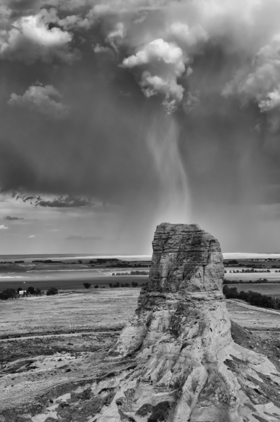 Narrow rain squall falling directly Jail Rock viewed from Courthouse Rock. Both Jail and Courthouse Rocks were important landmarks along the Oregon Trail, Nebraska.