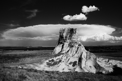 Expansive thunder cloud behind Jail Rock viewed from saddle with Courthouse Rock. Nebraska.