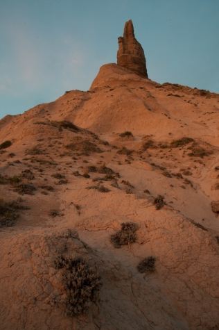 Chimney Rock viewed from eroded badlands at the west base in evening light.